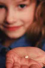 Picture of a young girl holding a tooth in her palm.